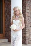 Beau portrait de mariage de jeune mariée tenant le bouquet posant dans la dentelle Photos libres de droits