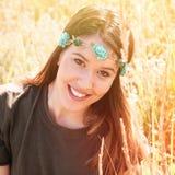 Beau portrait de sourire de boho de jeune femme avec la bande principale avec des fleurs dans le pré d'été photographie stock libre de droits