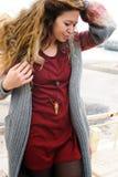 Beau portrait de sourire heureux de femme se reposant sur une rampe contre la mer d'automne, les longs poils, la robe rouge foncé Photographie stock