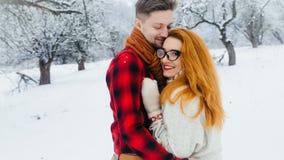 Beau portrait des amants étreignants dans la forêt neigeuse la belle femme rouge de sourire avec des verres Photo libre de droits