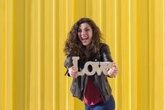 Beau portrait heureux de jeune femme tenant l'AMOUR Word au-dessus du yel Photo libre de droits