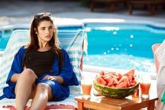 Beau prendre un bain de soleil de fille de brune, se trouvant sur le cabriolet près de la piscine Image libre de droits