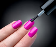 Beau processus de manucure. Le vernis à ongles étant appliqué à la main, poli est une couleur rose. Photos stock