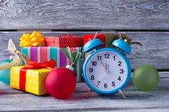 Beau réveil bleu parmi des cadeaux et des boules de Noël Photographie stock