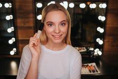 Beau regard gentil de jeune femme sur la caméra et la pose Elle tiennent des lipgloss à disposition Femme dans la chambre de beau photo stock