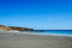 beau rivage sans fin prochain TU de plage sablonneuse la mer bleue clair comme de l'eau de roche au milieu du paysage aride photo stock