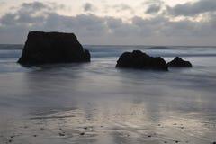 Beau rocha étonnant du DA de praia de plage sablonneuse au crépuscule Photos stock