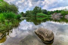 Beau rocher de rivière avec les nuages orageux de ciel, l'eau mobile Photos libres de droits