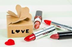 Beau rouge à lèvres rouge de luxe avec le cadeau de boîte d'amour Photographie stock