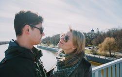 Beau s'aimant le couple se tient sur le pont souriant et embrassant Image stock