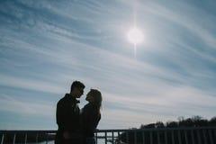 Beau s'aimant le couple se tient sur le pont souriant et embrassant Photos stock
