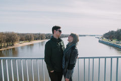 Beau s'aimant le couple se tient sur le pont souriant et embrassant Photos libres de droits