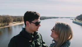 Beau s'aimant le couple se tient sur le pont souriant et embrassant Images stock