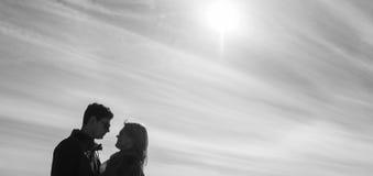Beau s'aimant le couple se tient sur le pont souriant et embrassant Photo stock