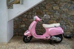 Beau scooter classique de Vespa de couleur de rose de conception avec le stationnement blanc de coussin sur le trottoir de lavage Images stock
