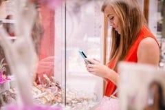 Beau service de mini-messages de femme tout en sélectionnant une montre-bracelet photos libres de droits