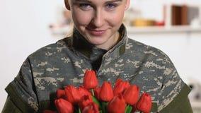 Beau soldat féminin tenant les tulipes rouges souriant sur la caméra, jour de forces armées banque de vidéos