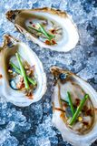 Beau Soleil oysters topped with chives and red pepper flakes Royalty Free Stock Image