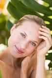 Beau sourire blond à l'appareil-photo derrière la feuille Photographie stock libre de droits
