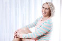 Beau sourire d'une cinquantaine d'années actif de femme amical et regard dans l'appareil-photo à la maison dans le salon Images stock