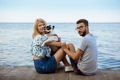 Beau sourire de couples, se reposant avec le bouledogue français près de la mer Image stock