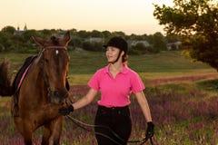 Beau sourire de jeune fille à sa concurrence d'uniforme de habillage de cheval : dehors portrait sur le coucher du soleil Images libres de droits