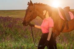 Beau sourire de jeune fille à sa concurrence d'uniforme de habillage de cheval : dehors portrait sur le coucher du soleil Fusée d Photos stock