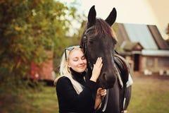 Beau sourire et yeux de fille blonde avec le cheval Image stock
