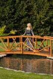 Beau support blond aux cheveux longs de femme sur un pont en bois au-dessus d'un ?tang artificiel, dans la bordure naturelle, fon image stock