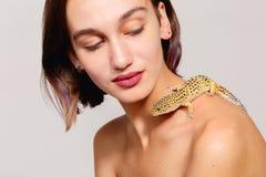 Beau sur un fond gris Le gecko d'iguane rampe au-dessus de ses épaules et la fille l'observe inside photographie stock libre de droits