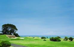 Beau terrain de golf vert par l'océan Image libre de droits