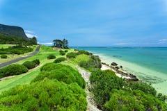 Beau terrain de golf vert par l'océan Photographie stock libre de droits