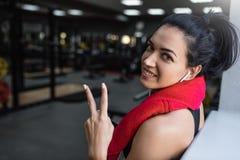 Beau tir de la jeune femme beautful heureuse de forme physique faisant une pause de sa séance d'entraînement avec la serviette ro photographie stock