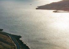 Beau tir de la mer à côté d'une route étroite photographie stock libre de droits