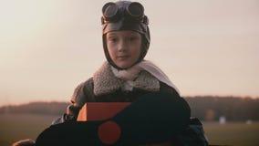 Beau tir de portrait de peu de fille dans le rétro costume pilote plat d'amusement regardant la caméra avec le mouvement lent de  banque de vidéos