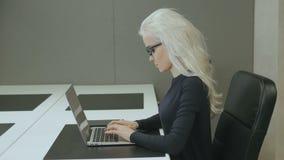 Beau travail de fille d'affaires dans le bureau avec l'ordinateur portable banque de vidéos