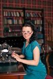 Beau typewritingin de femme de brune la bibliothèque. photo de style ancien images libres de droits