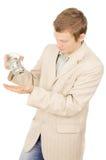 Beau un jeune type essayant d'extraire l'argent à partir d'un conta en verre Photographie stock