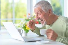 Beau vieil homme avec un ordinateur portable Photographie stock libre de droits