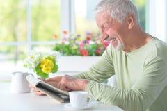 Beau vieil homme lisant un journal Photographie stock