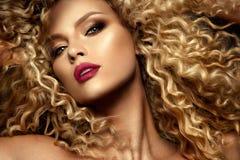 Beau visage d'un mannequin avec des yeux bleus Cheveu bouclé Languettes rouges Images libres de droits