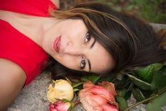 Beau visage de fille de brune avec la robe rouge à côté du groupe de roses, à l'extérieur images libres de droits