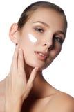 Beau visage de jeune femme avec de la crème cosmétique sur une joue Images libres de droits
