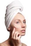 Beau visage de jeune femme avec de la crème cosmétique sur une joue Concept de soin de peau Portrait de plan rapproché d'isolemen Photographie stock libre de droits