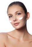 Beau visage de jeune femme avec de la crème cosmétique sur une joue Concept de soin de peau Portrait de plan rapproché d'isolemen Photo stock