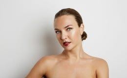 Beau visage de jeune femme avec la fin fraîche propre de peau sur le blanc Photo stock