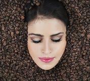 Beau visage parmi des haricots de coffe Photographie stock
