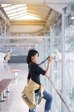 Beau voyageur asiatique de femme à l'aide de l'appareil photo numérique dans l'aéroport Image stock