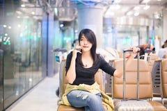 Beau voyageur asiatique de femme à l'aide du téléphone portable dans l'aéroport Photo libre de droits