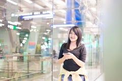 Beau voyageur asiatique de femme à l'aide du téléphone portable dans l'aéroport Photos stock